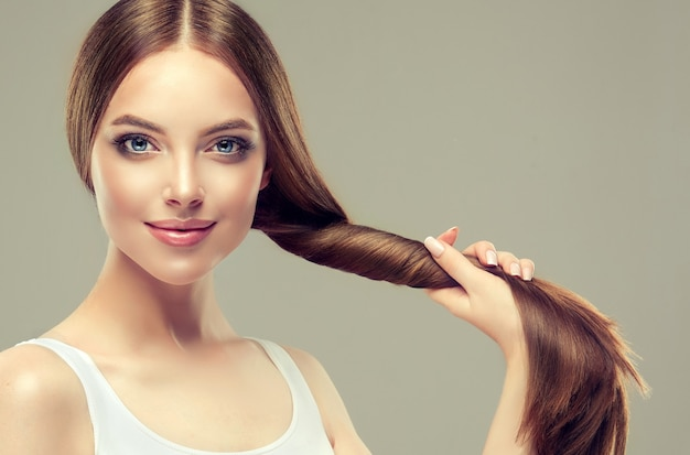 Beautiful model with long, dense, straight hair and vivid makeup, is holding in the palm tail of well groomed and healthy hair.
