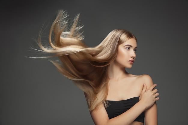 어두운 회색 스튜디오 배경에 고립 된 긴 부드럽고 비행 금발 머리를 가진 아름 다운 모델. 잘 관리 된 피부와 머리가 공기에 날리는 젊은 백인 모델.