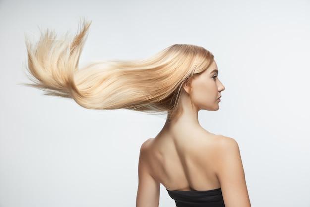 白いスタジオの背景に分離された長く滑らかな、飛んでいるブロンドの髪を持つ美しいモデル。手入れの行き届いた肌と髪が空気を吹いている若い白人モデル。