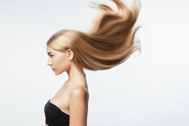 흰색 스튜디오 배경에 고립 된 긴 부드럽고 비행 금발 머리를 가진 아름 다운 모델. 잘 관리 된 피부와 머리가 공기에 날리는 젊은 백인 모델.