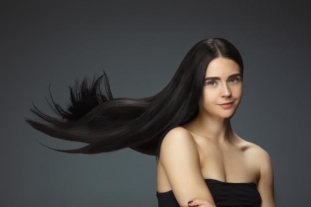 長く滑らかな、飛んでいるブルネットの髪の美しいモデル