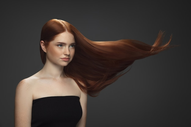 Beautiful model with long smooth, flying red hair isolated on dark