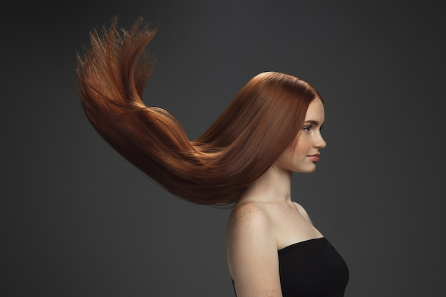 어둠에 고립 된 길고 부드럽고 비행 빨간 머리를 가진 아름다운 모델