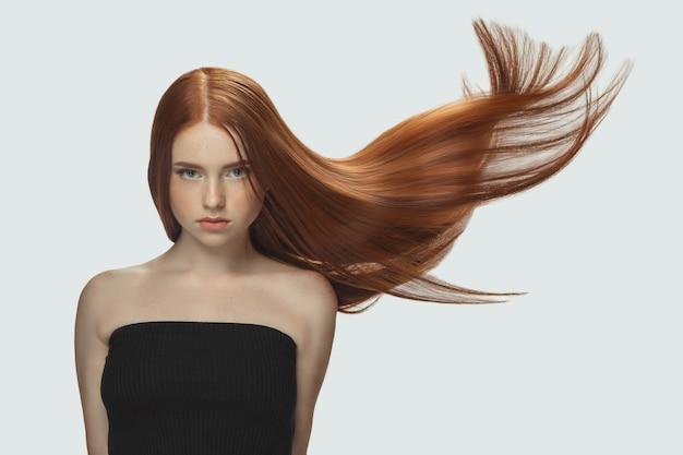 흰색 스튜디오 배경에 격리된 길고 매끄럽고 날아다니는 빨간 머리를 가진 아름다운 모델입니다.