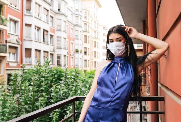 코로나 바이러스 전염병 코로나 19로 인해 마스크가있는 아름다운 모델이 멋진 파란 드레스로 집 발코니에서 카마라를보고 있습니다.