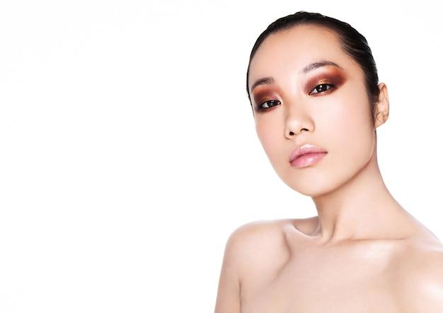 自然で健康的な輝く肌と白い背景で隔離の暗いアイメイクの美しいモデル Premium写真