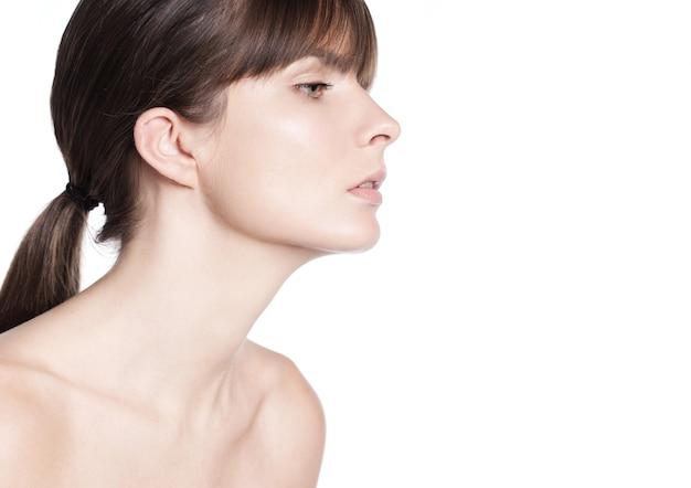 白い背景で隔離の自然で健康的な輝く肌を持つ美しいモデル Premium写真