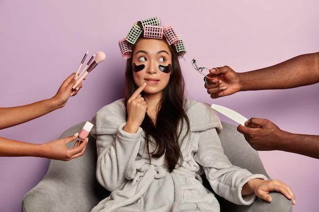 Красивая модель с задумчивым выражением лица, с повязками на глазах, в окружении косметологического оборудования