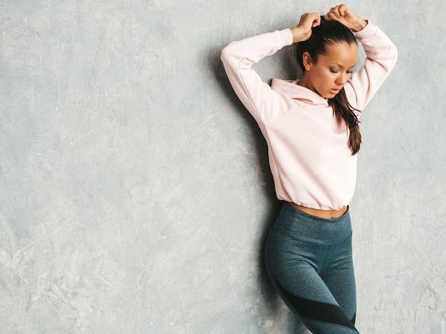 完璧な日焼けした体を持つ美しいモデル。灰色の壁の近くのスタジオでポーズをとる女性