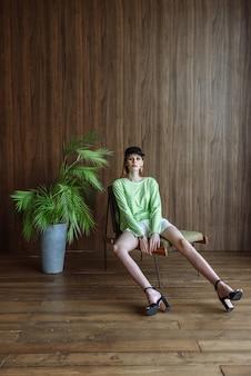 スタジオで服の新しい夏のコレクションでポーズをとって座っている美しいモデルの女性