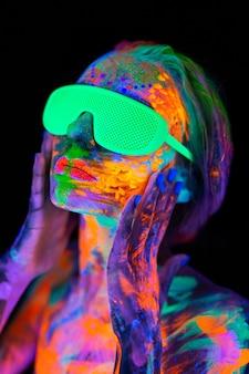ネオンの光、ナイトクラブ ディスコの中でカラフルな明るい蛍光化粧をした眼鏡をかけた美しいモデルの女性。