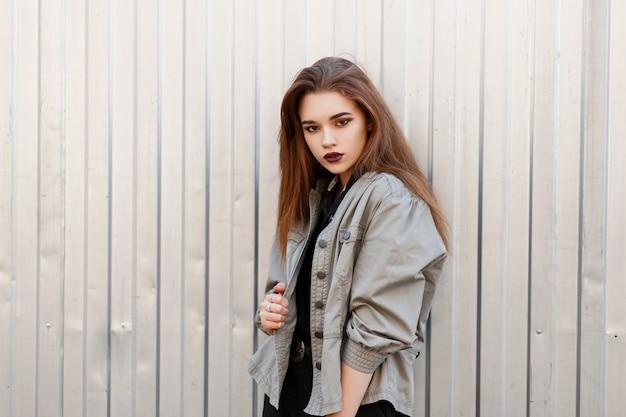 금속 벽 근처 포즈 유행 재킷에 어두운 입술을 가진 아름다운 모델 여자 ¹