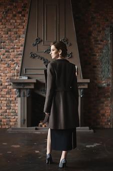 빈티지 인테리어에 포즈 유행 코트에 슬림 바디와 아름 다운 모델 여자
