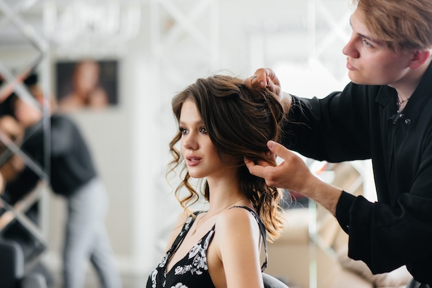 In a beautiful, modern beauty salon, a professional stylist makes a haircut and hairstyle for a young girl. beauty, and fashion.