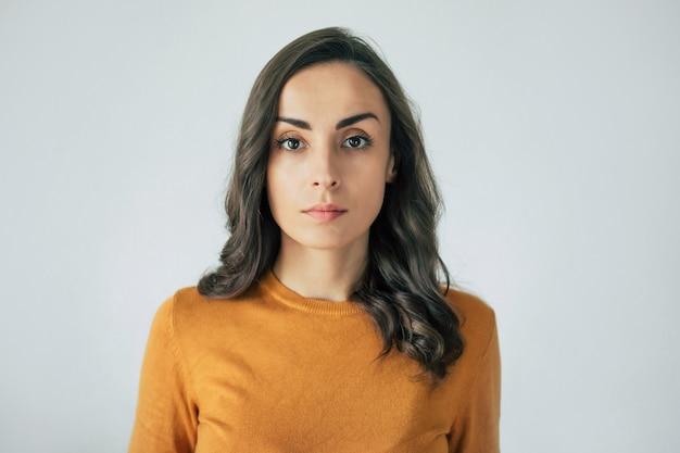 Красивый современный уверенно портрет женщины брюнет с вьющимися волосами, пока она смотрит в камеру.