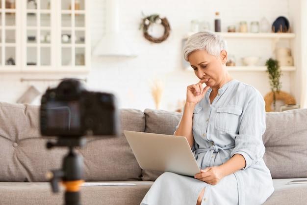 Bella donna anziana moderna dai capelli grigi in abiti eleganti che lavorano in remoto utilizzando il computer portatile, digitando un messaggio, avendo espressione facciale premurosa, seduto sul divano