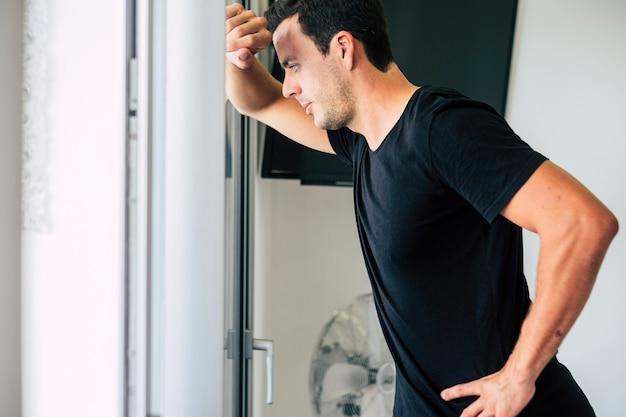 Красивый современный модный молодой человек дома теряется в своих мыслях возле оконной двери
