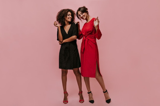 Beautiful modern girl with curly hair in black outfit and trendy heels smiling and looking at cool girl in red dress on pink wall