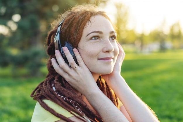 Beautiful modern girl with dreadlocks listening to music with headphones in autumn sunny park