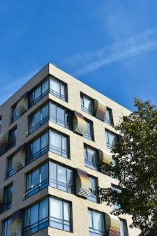 Красивый современный дом с большими окнами на фоне голубого неба.