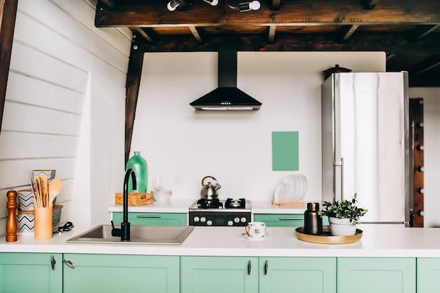 調理器具付きの美しいモダンなキッチン。白いきれいなプレートが付いている皿乾燥ラック
