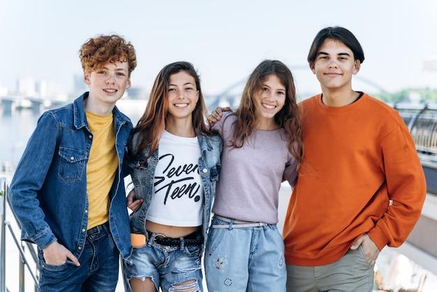 아름답고 현대적이며 웃고 있는 십대들이 도시를 배경으로 포즈를 취하고 있습니다. 긍정적인 아이들 - 십대들이 포즈를 취하고 있습니다.