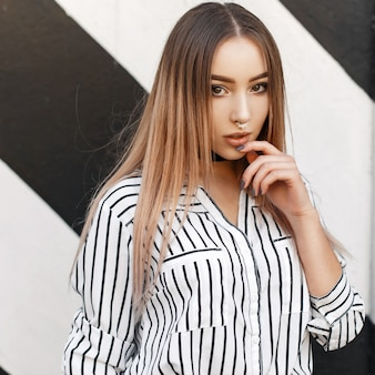 Красивая девушка в современном стиле с серьгами в носу в модной полосатой блузке у стены