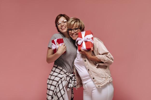 Belle due donne moderne con acconciatura corta e occhiali in pantaloni bianchi sorridenti, abbracciando e tenendo scatole regalo rosse su sfondo rosa.
