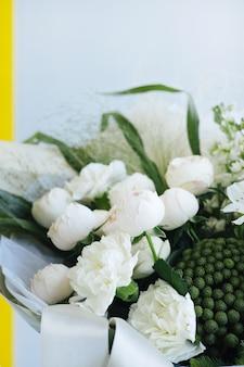 白いバラの美しいモダンなウェディングブーケ。フラワーショップと配達のコンセプト。休日のプレゼント、母の日の側面図垂直