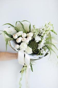 手に白いバラと美しいモダンなウェディングブーケ。フラワーショップと配達のコンセプト。ホリデープレゼント、母の日サイド縦