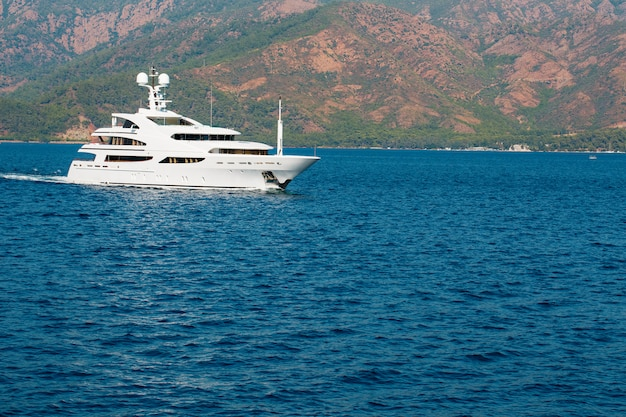 Beautiful modern white yacht with sail on the blue sea