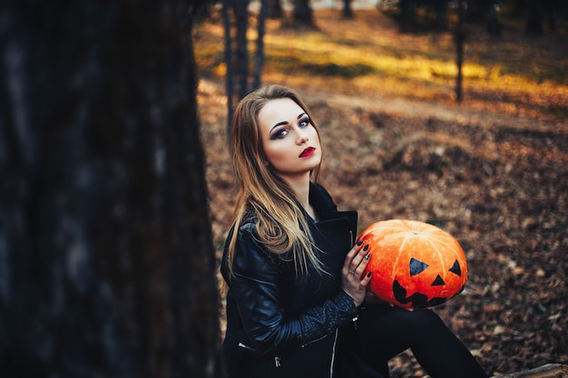 Beautiful modern witch holding halloween pumpkin in the forest. october. happy holidays
