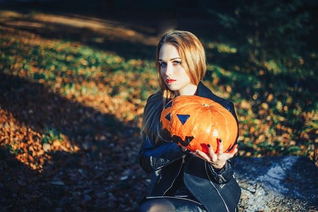 フォレスト内のハロウィーンカボチャを保持している美しいモダンな魔女。 10月。幸せな休日