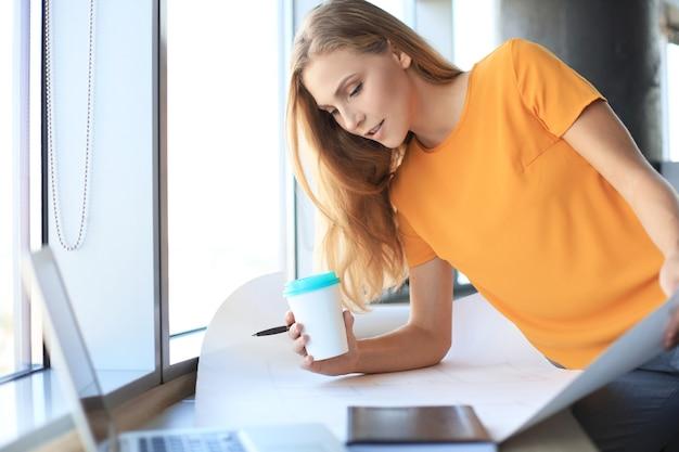 아름다운 현대 여성이 창의적인 사무실에서 일하는 동안 청사진에 뭔가를 쓰고 있습니다.