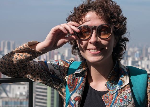 백그라운드에서 상파울루시와 선글라스를 착용하는 카메라에 포즈를 취하는 아름답고 현대적인 여성.