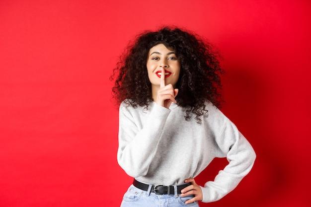 Bella donna moderna con capelli ricci e trucco, zitto e sorridente, raccontando un segreto, facendo sorpresa e sorridendo, in piedi su sfondo rosso