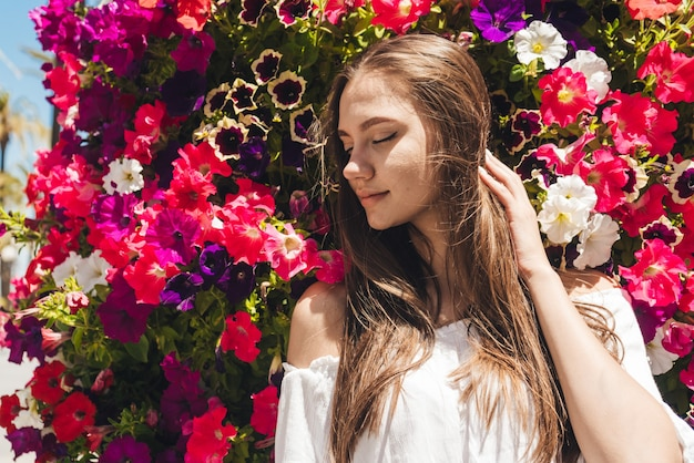 Beautiful moldavian woman with marvelous hair, covering her eyes in bliss stands on a background of bright flowers
