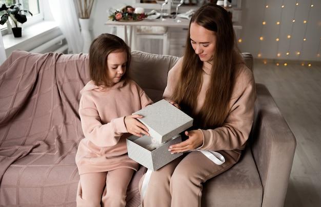 美しいママと娘がソファに座って贈り物を開いています