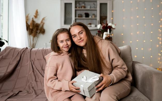 Красивая мама и дочка сидят на диване с подарком и смотрят в камеру