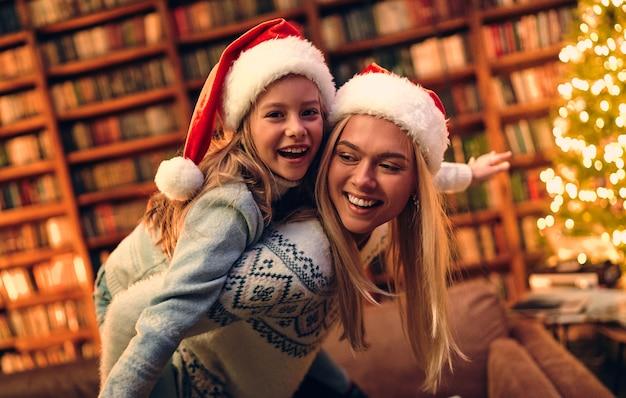 Красивая мама и дочка, новогодние шапки, елочные огни. портретный праздник. зимний фон. семейный детский портрет. новогоднее украшение.