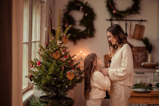 クリスマスツリーの近くの美しいママと娘