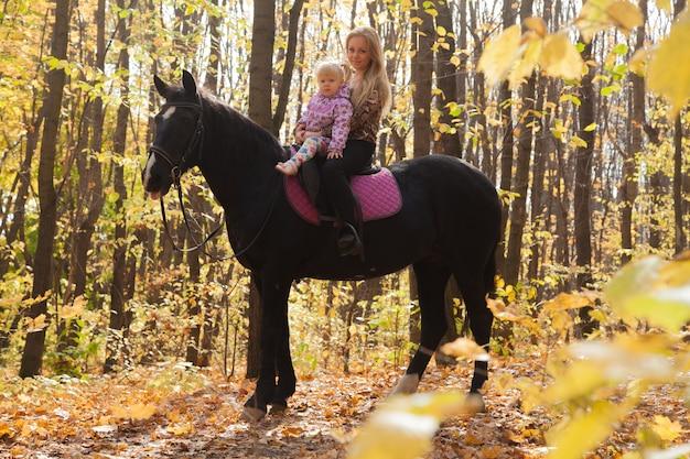 가을 숲에서 말을 타고 아름다운 엄마와 딸