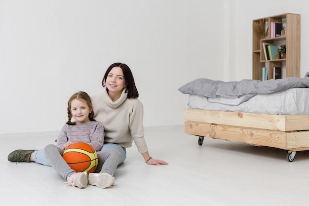 Красивая мама и дочь позирует в помещении