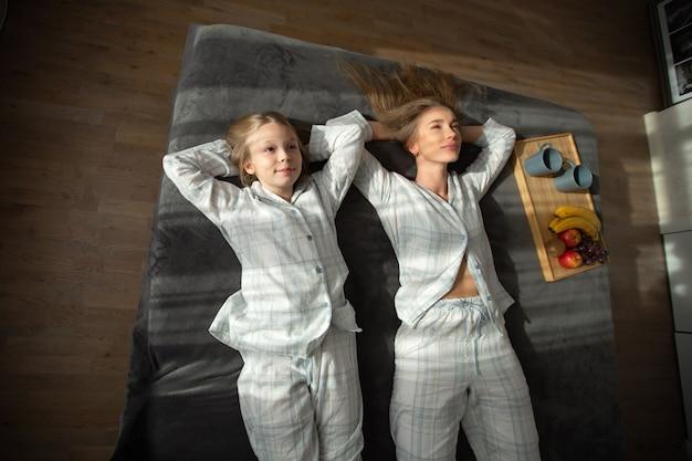 Красивая мама и дочь, сидя в постели
