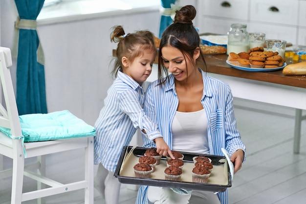 美しいお母さんが娘のために新鮮なクッキーを焼き、キッチの自宅のトレイにスイーツを持ってきました