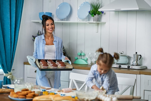 Beautiful mom baked fresh cookies for her daughter and brought sweets on a tray at home in the kitchen
