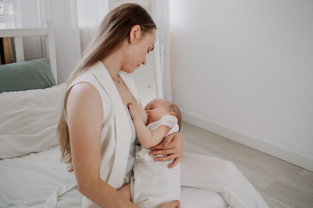 Красивая мама кормит грудью девочку на кровати в спальне