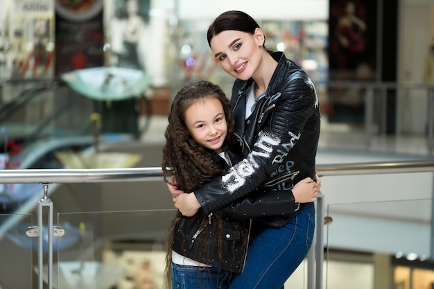 Beautiful mom and daughter smiling while shopping at the mall