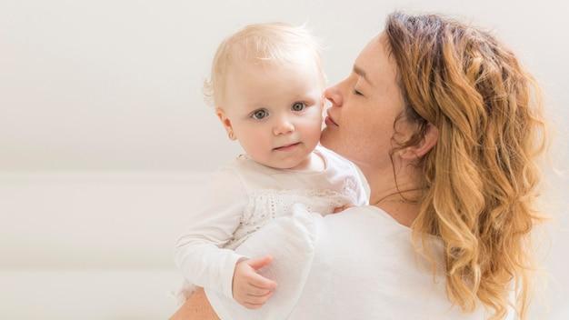 彼女の女の赤ちゃんを保持している美しいお母さん