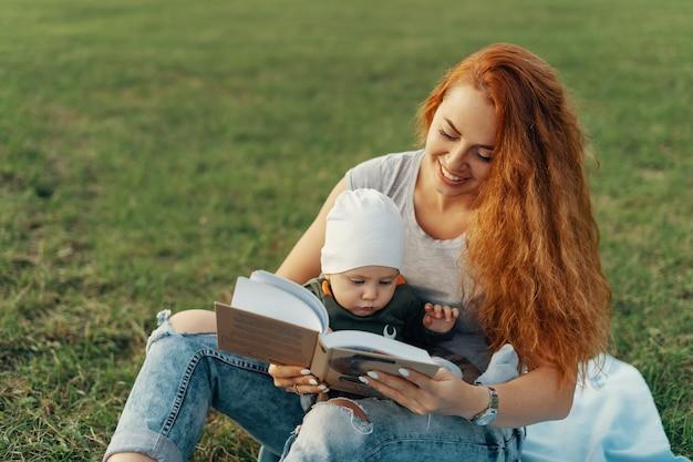 美しいお母さんはかわいい男の子と一緒に本を読んでいます